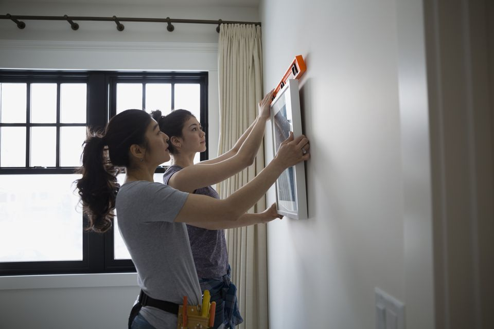 Mother and teenage daughter hanging art with a level tool