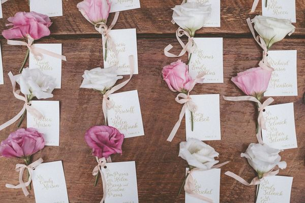 Escort cards with roses tied to them