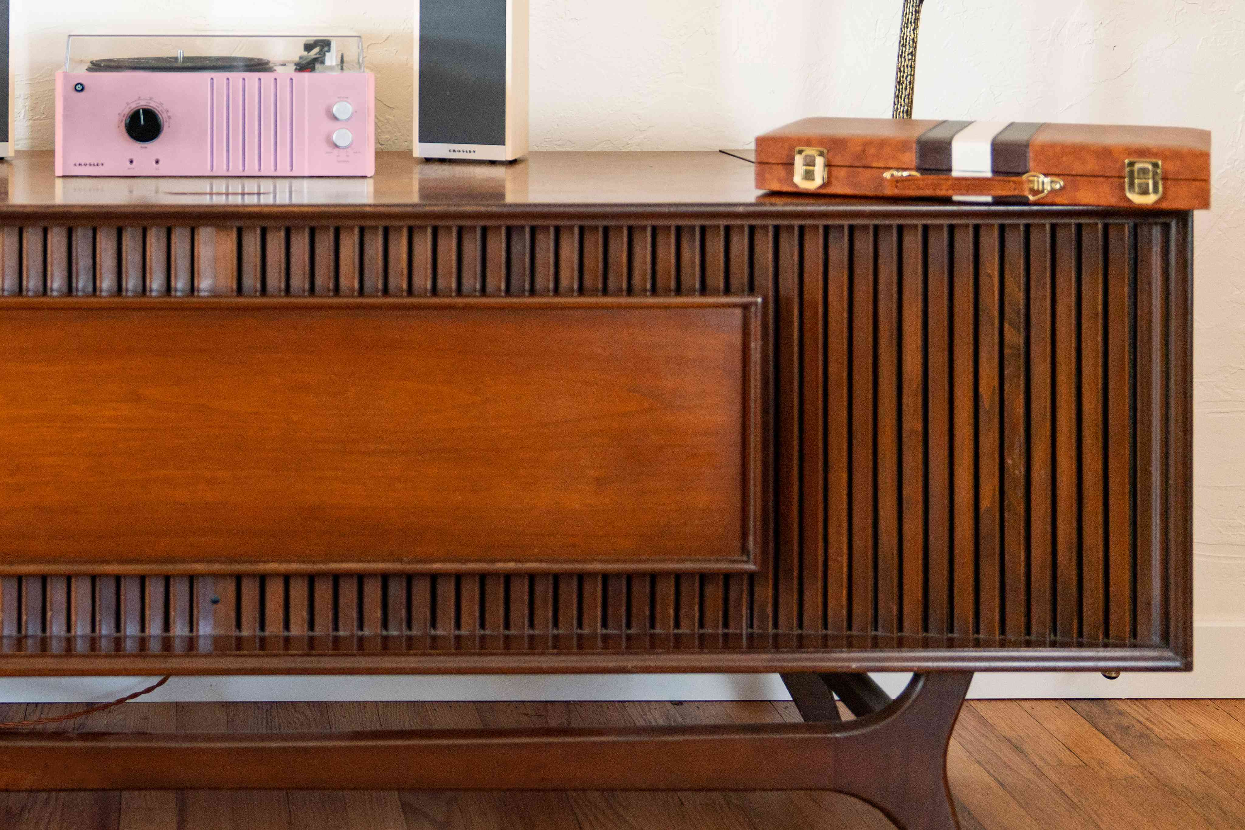 Mid-century modern styled cabinet with sleek lines in front and decor items on top closeup