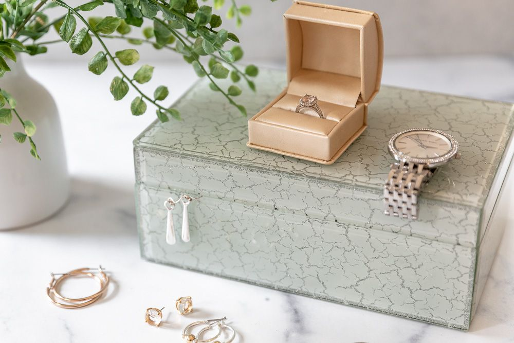 Old jewelry surrounding vintage jewelry box next to houseplant to be sold for cash
