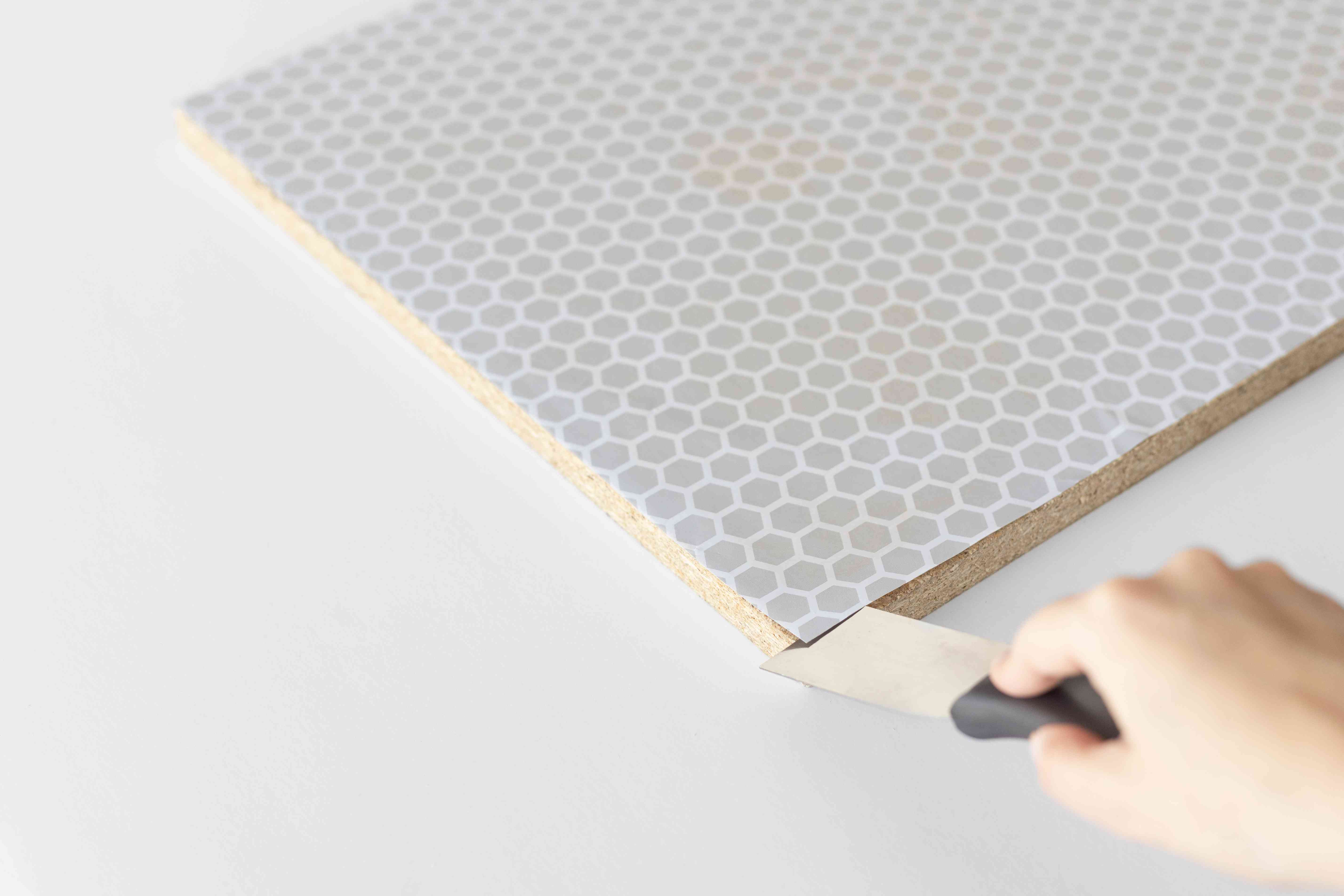 using a putty knife to peel back shelf paper