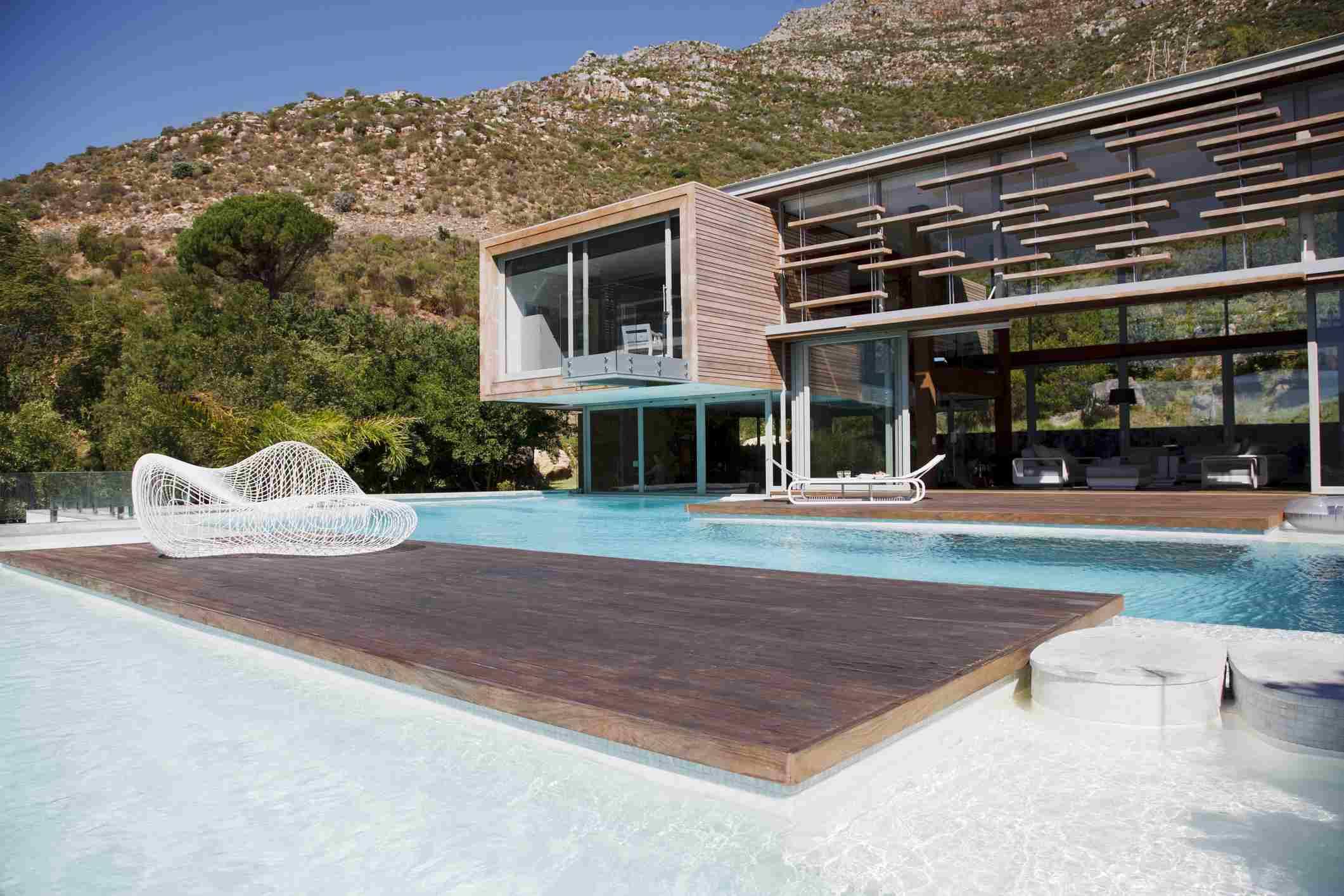 Una piscina moderna con casa moderna cerca de las montañas