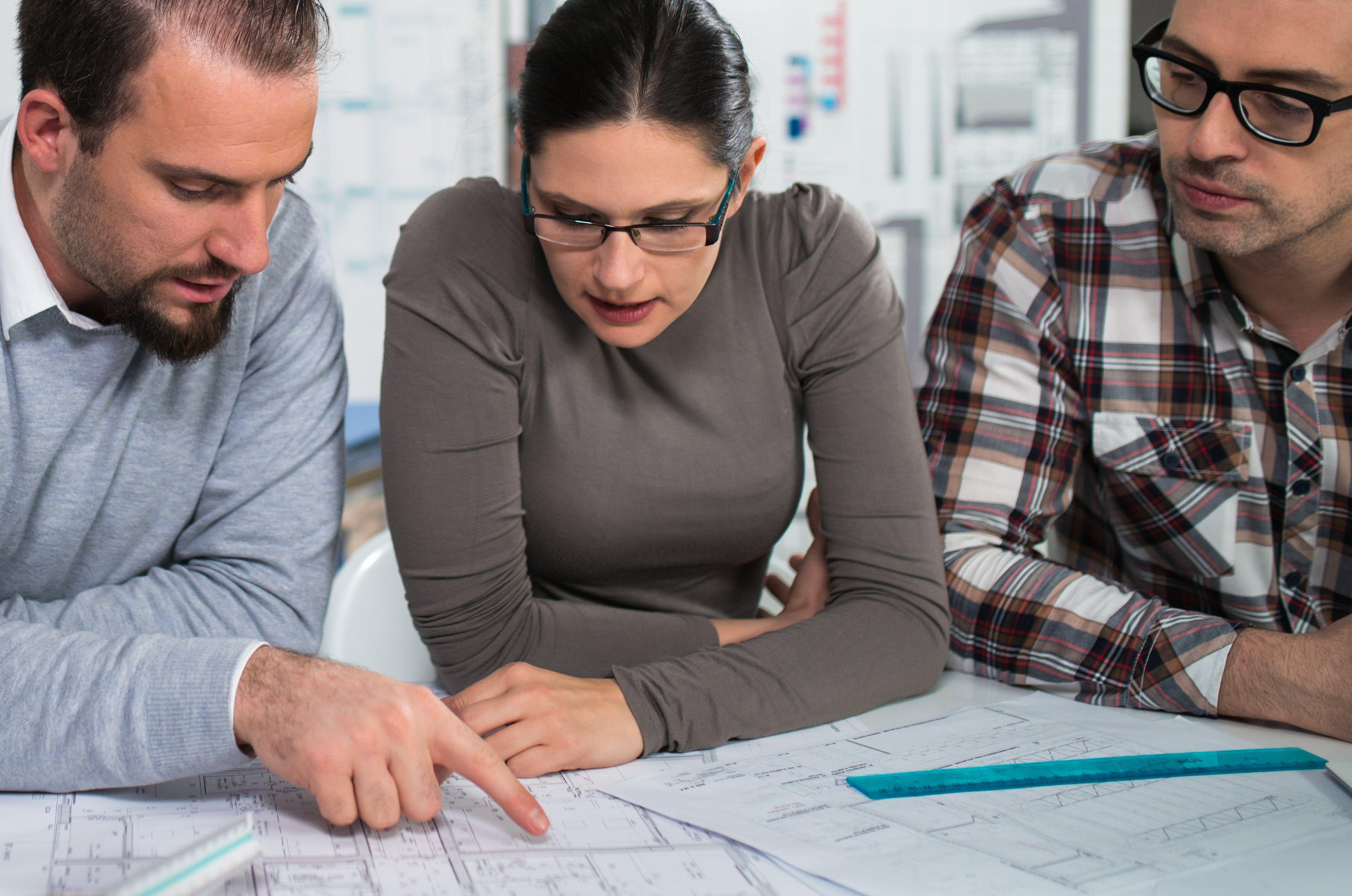 Tres personas mirando planos de casas