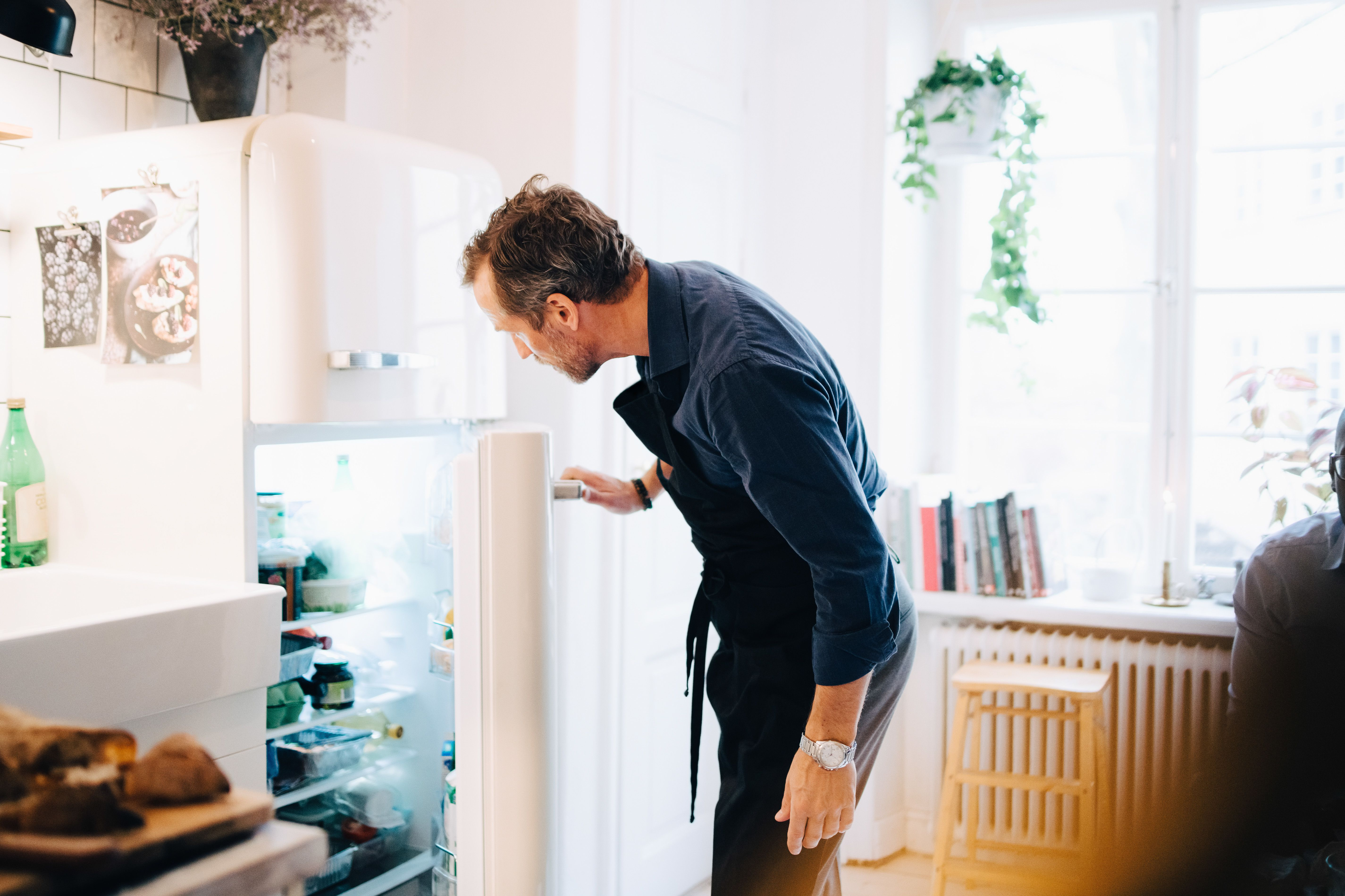 Man looking into refrigerator while standing at kitchen.