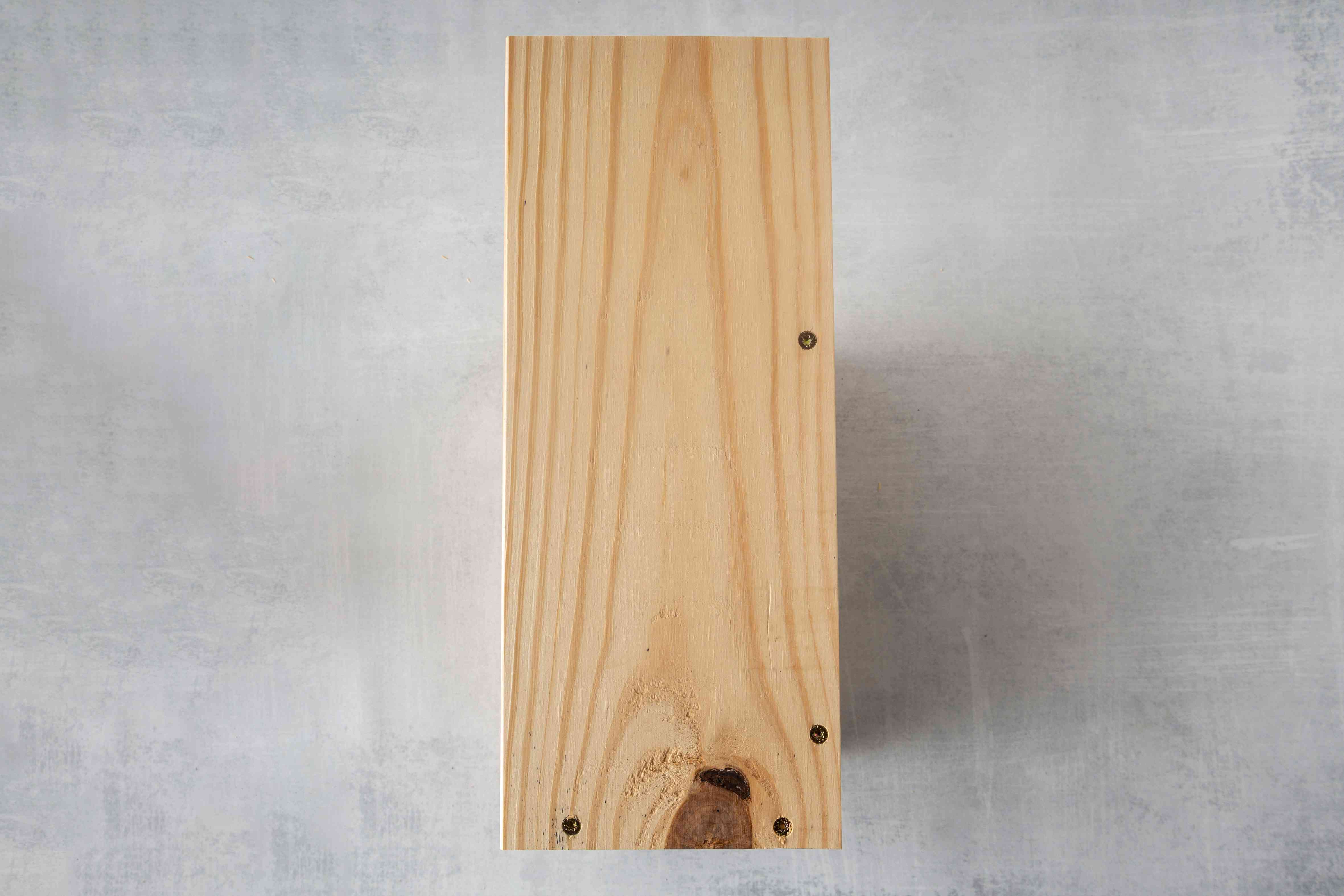 A pine board with screws.