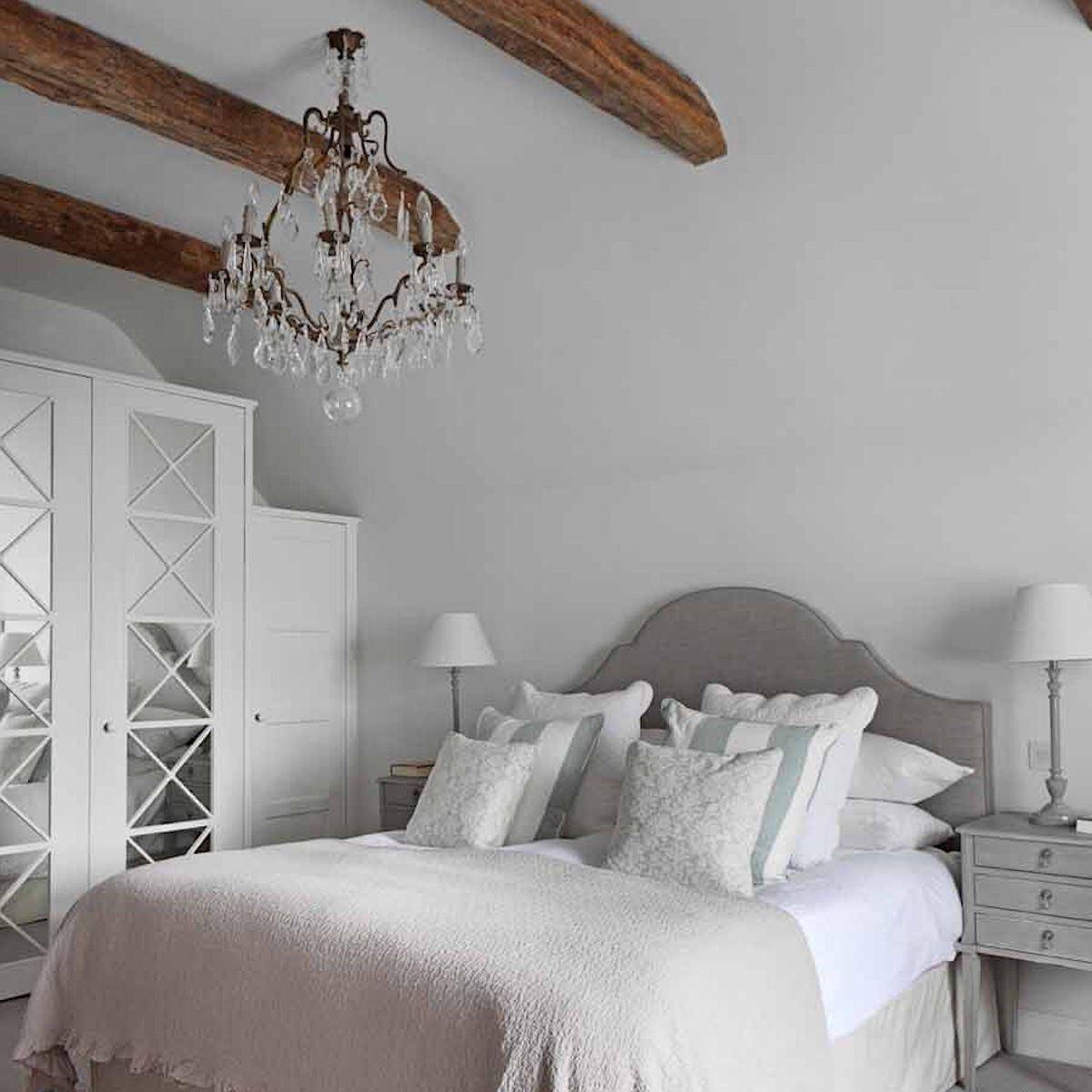 bedroom with white walls, neutral colors with light touches of blue, exposed wooden beams on ceiling, ornate chandelier, tuscan style