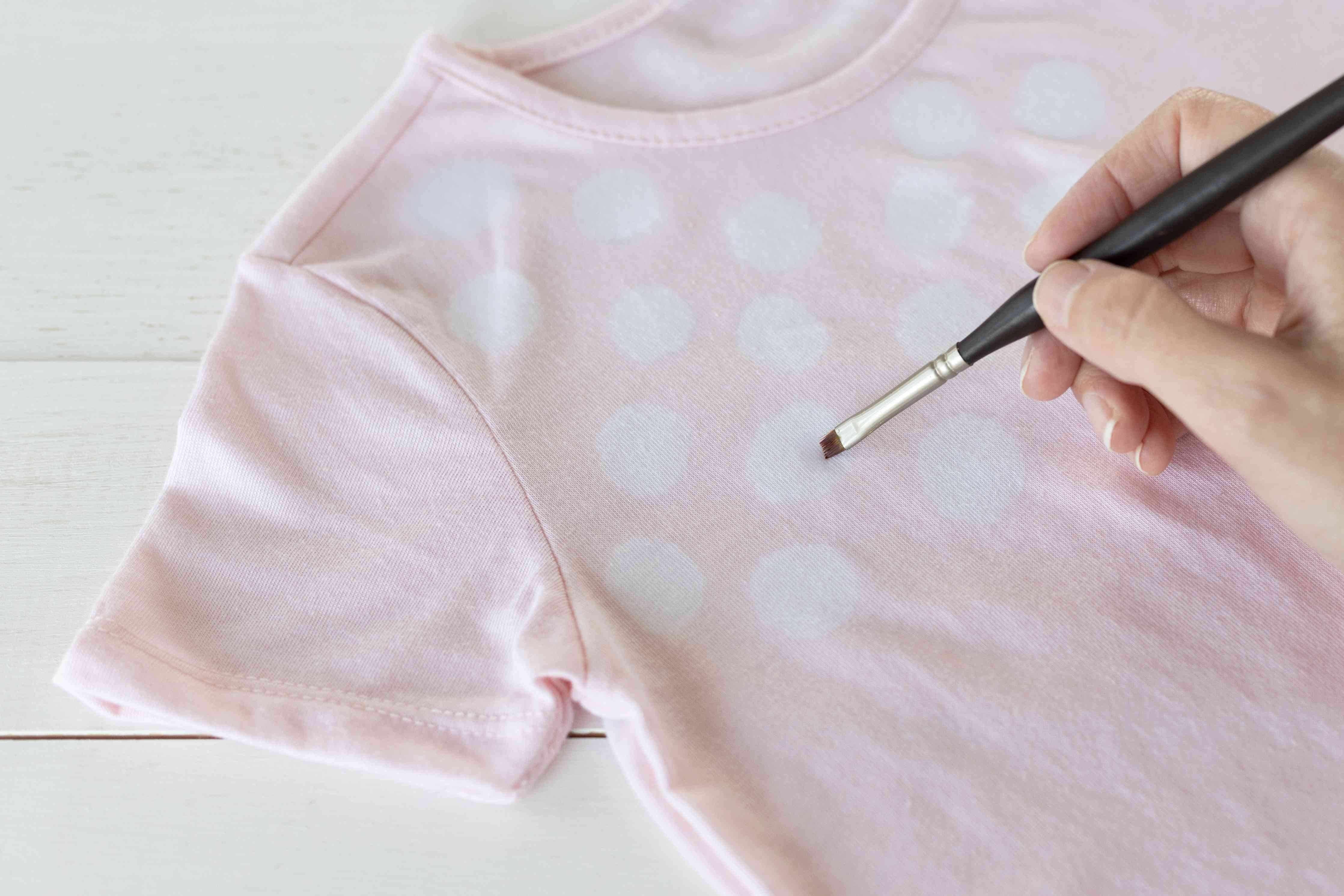 Pink shirt with white circle painted with small brush and bleach