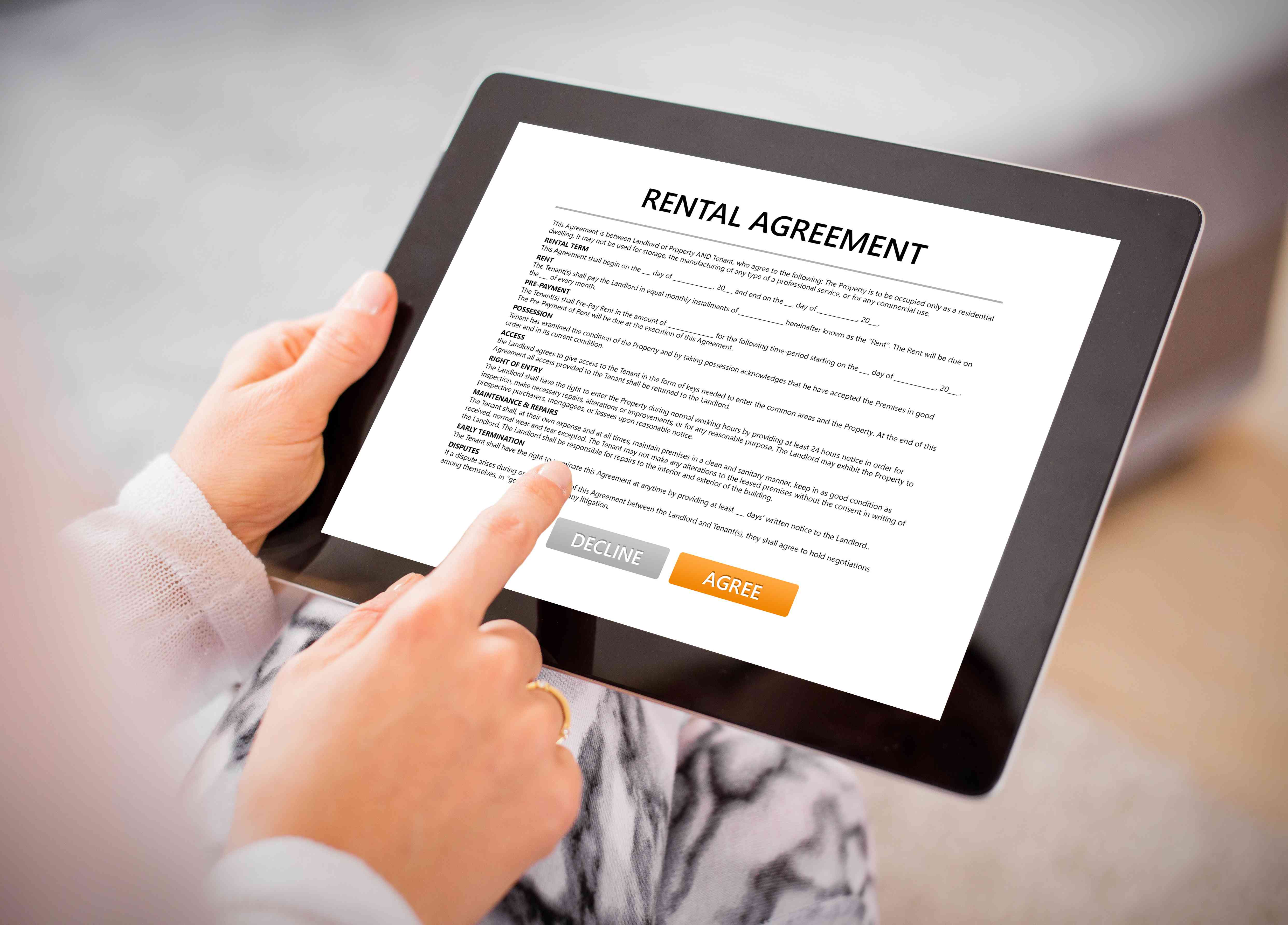 Woman reading rental agreement on tablet.