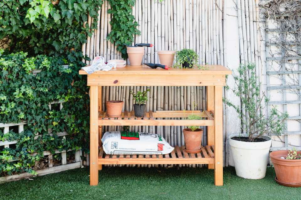 Potting bench made from plans with potting materials and plants in containers outside in backyard