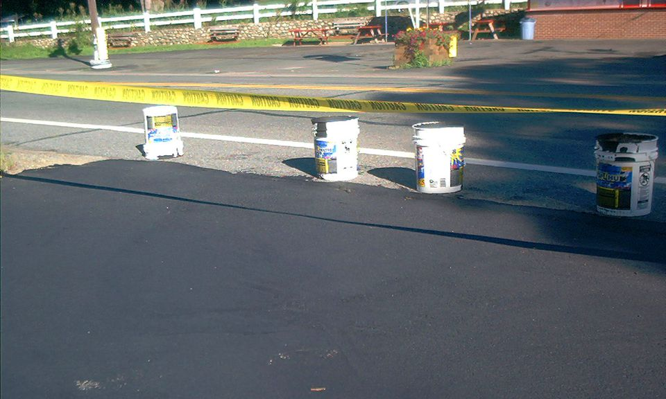 Put barricade tape (image) for a newly-sealed driveway to keep cars away. The sealant must dry.