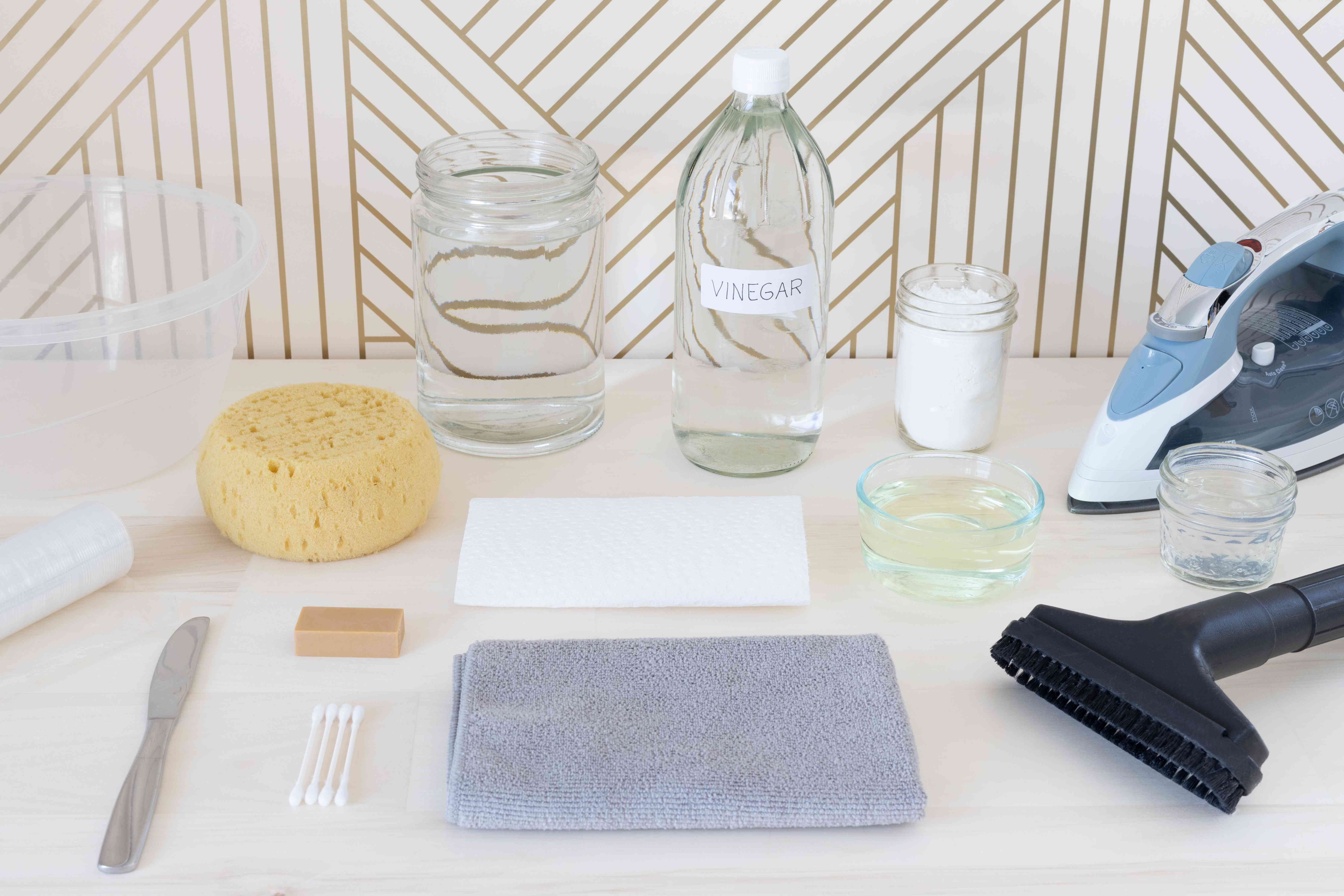 Materials and tools laid in front of white and gold striped wallpaper for cleaning
