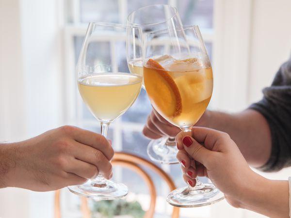 Three people toasting glasses together