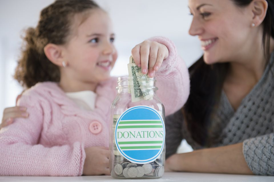 Girl putting money in donation jar
