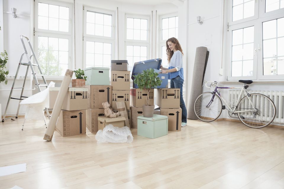 Woman in new apartment unpacking cardboard box