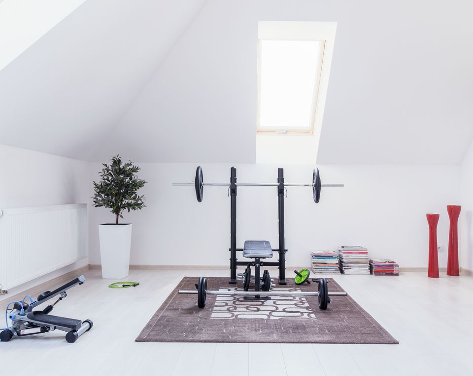 A home gym with a slanted roof and equipment on the ground
