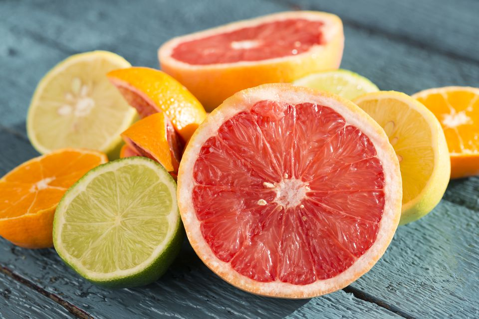 Lemons, limes and grapefruits sliced open on a board