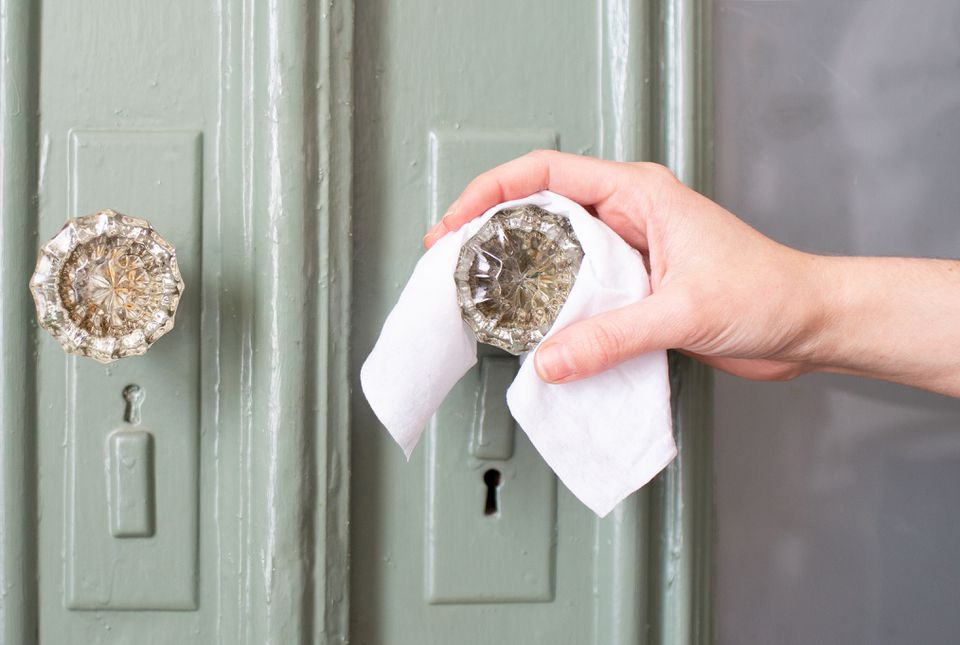 woman wiping off a doorknob with disinfectant wipes