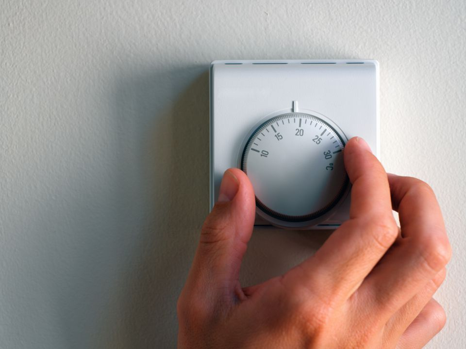 Hand turning a thermostat knob