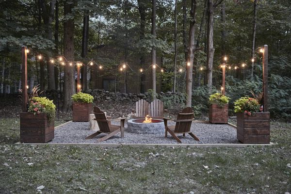 String lights hung up around outdoor lounge chairs and firepit