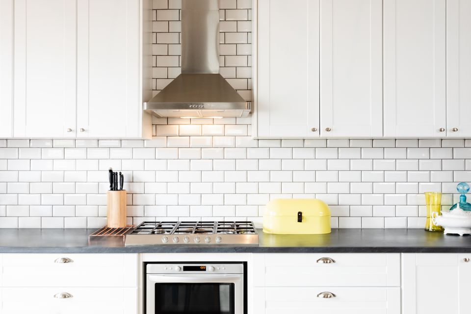 Used white cabinets installed in modern kitchen with white brick wall