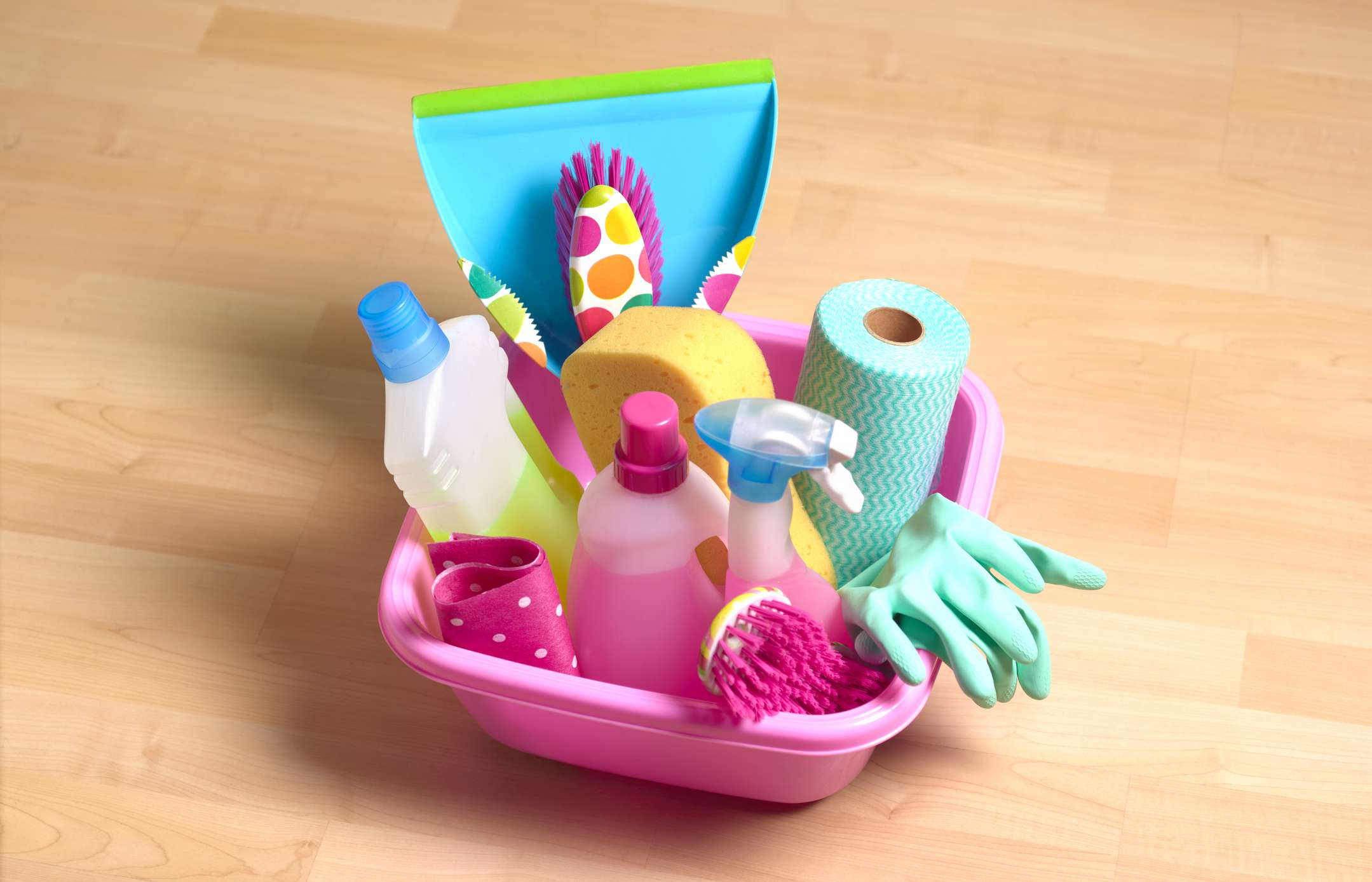 A pink shower caddy filled with cleaning supplies.