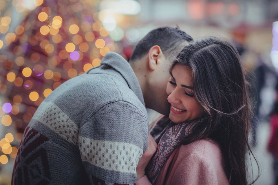 Couple kissing in front of twinkle lights
