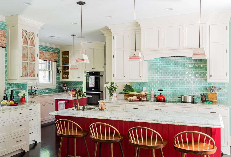 kitchen with teal backsplash and red island