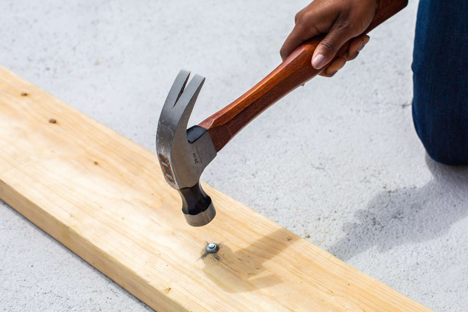 Hammer driving nail into wooden board till flushed