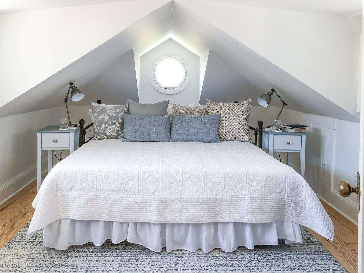 Upgraded attic guest bedroom with white walls and day bed.