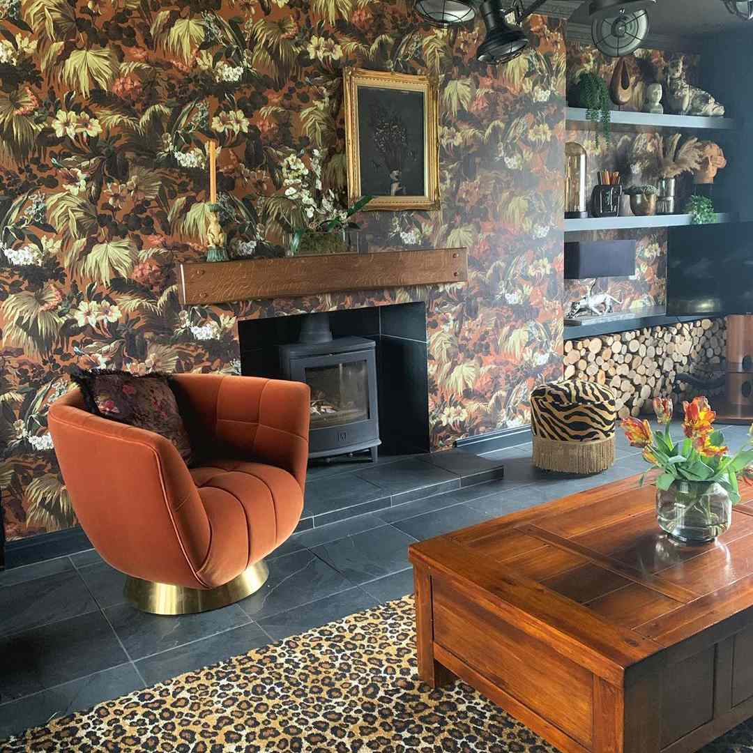 Living room with orange chair and brown wallpaper