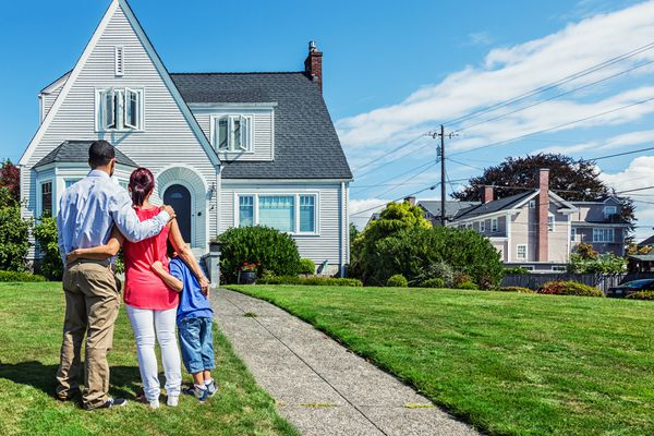 A young family stands outside a home