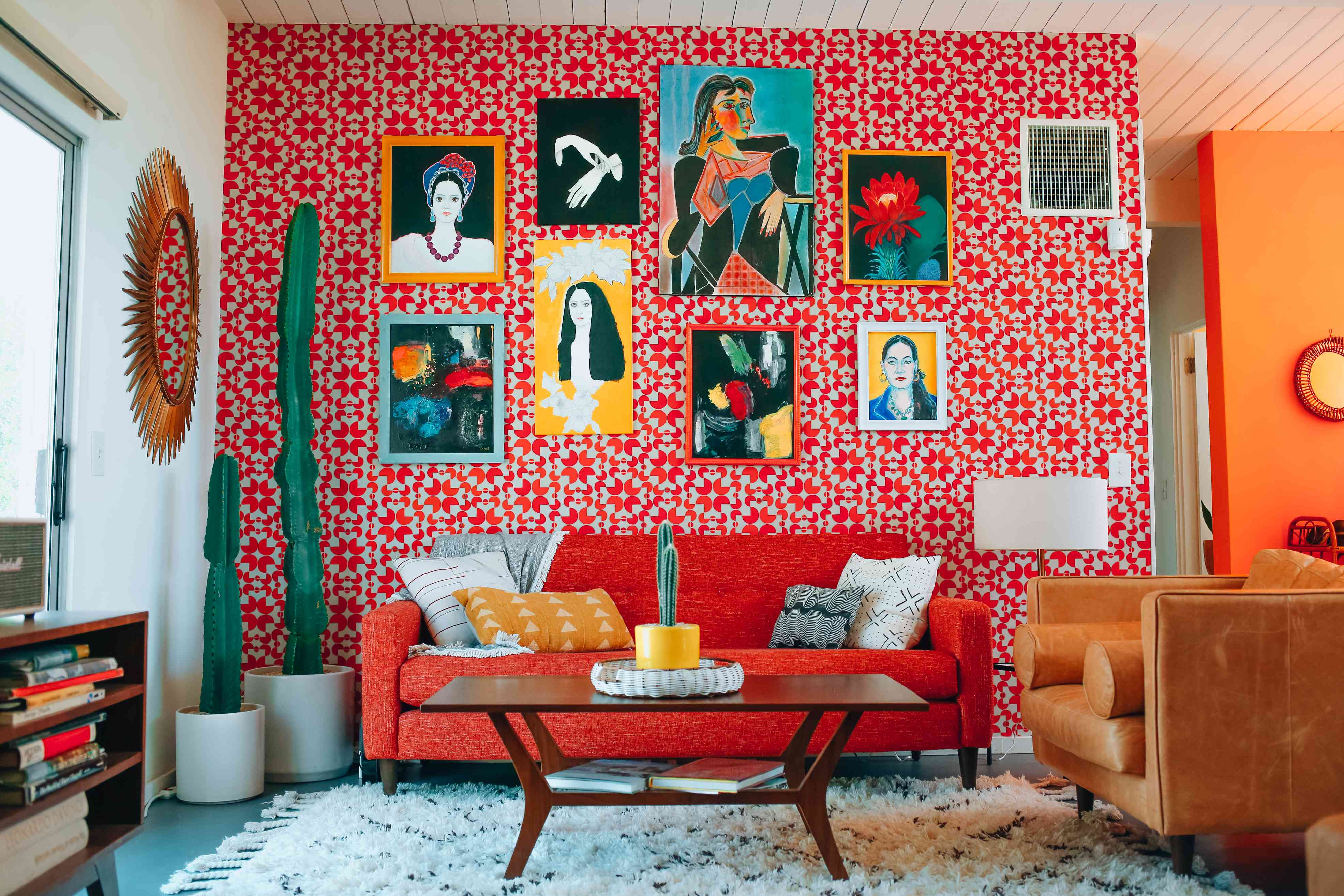Bright red wallpaper with artwork in a living room