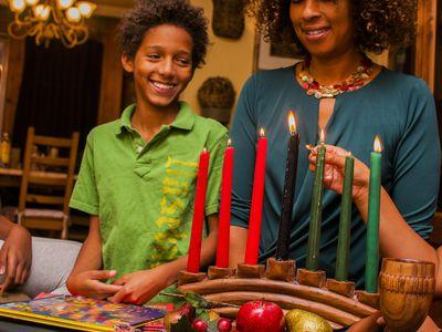 Family lighting kinara candles, celebrating Kwanzaa