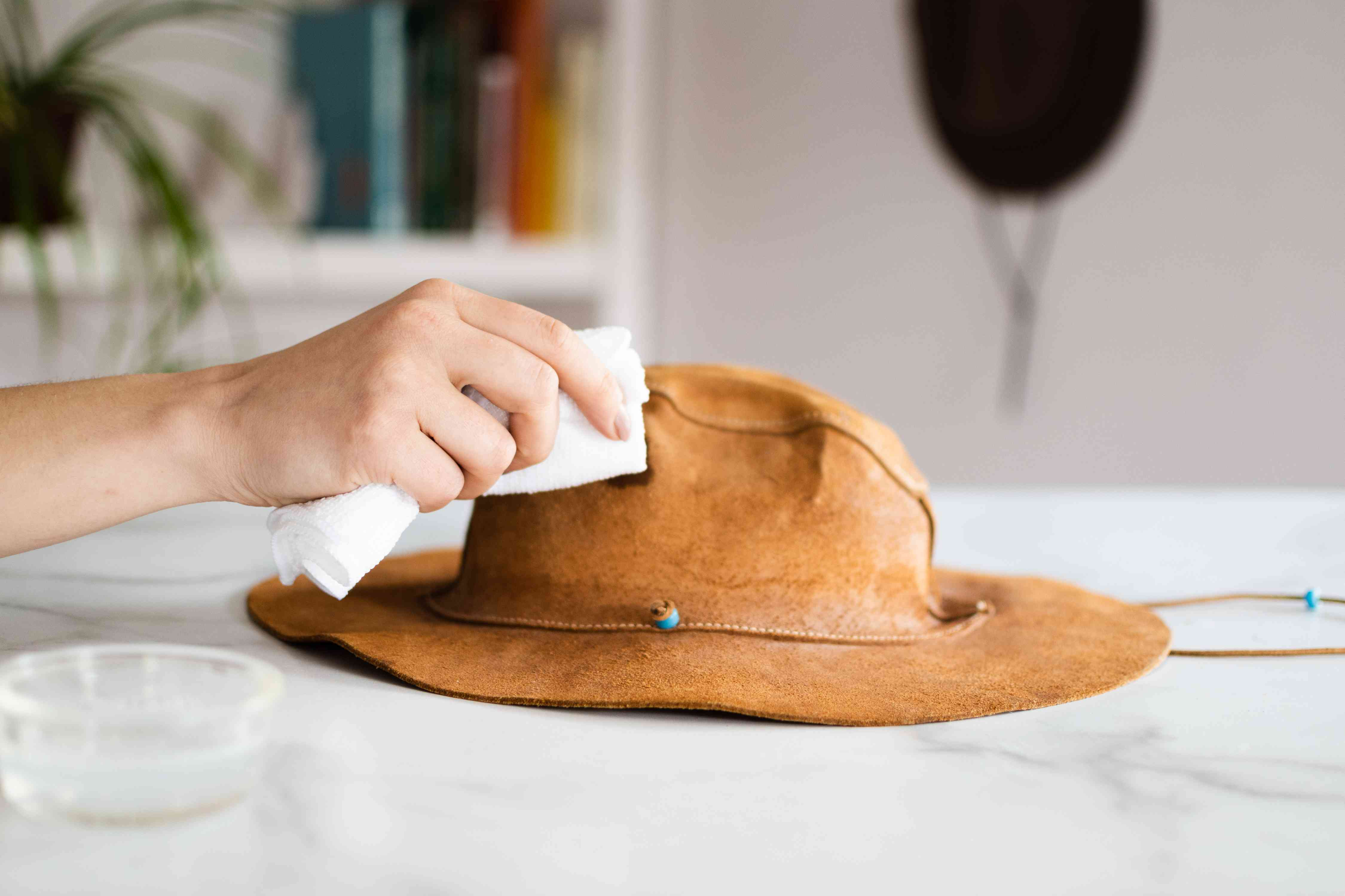 White cloth with mild detergent wiping stain on light brown suede leather hat