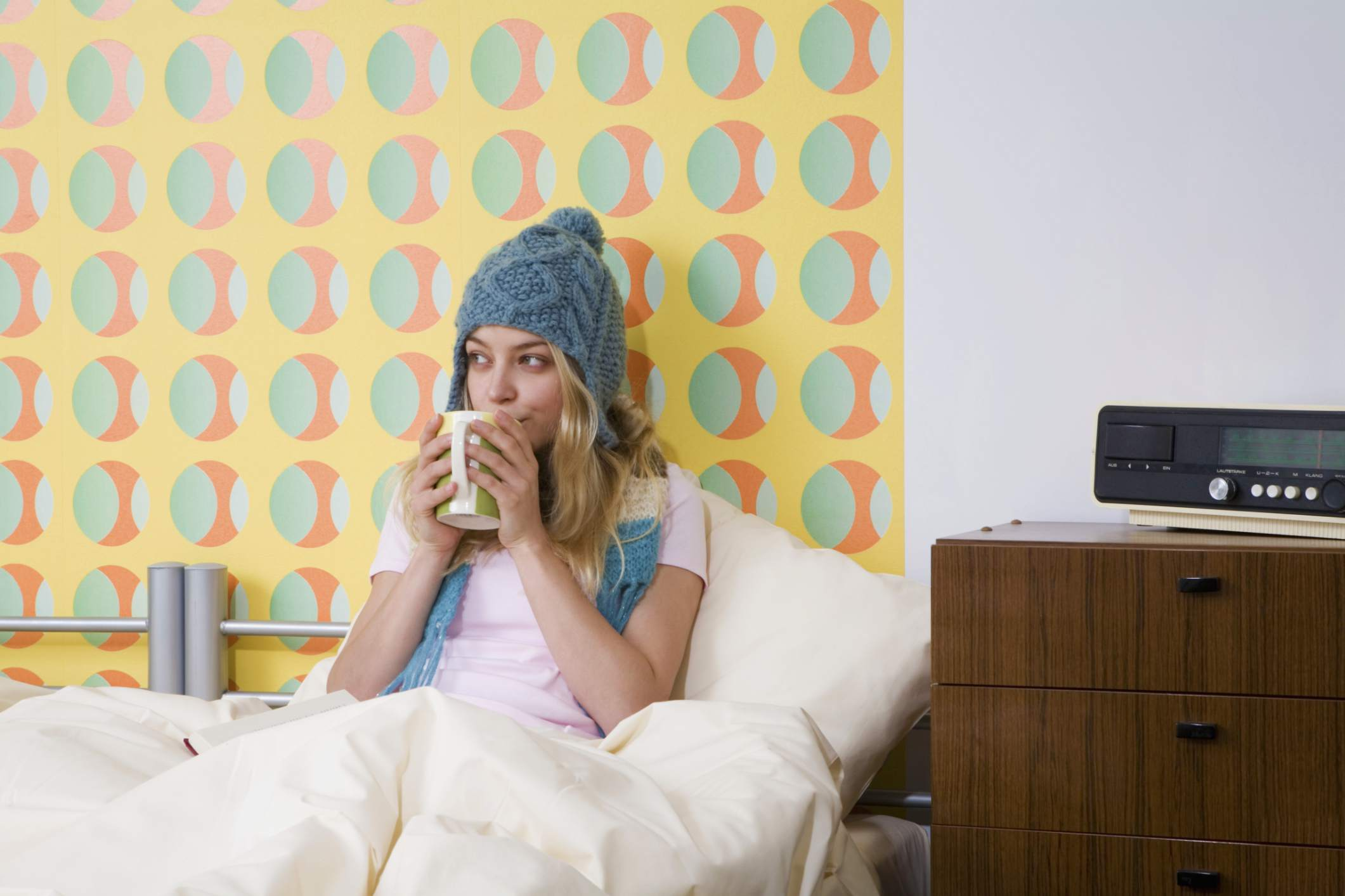 woman dressed warmly in bed with coffee
