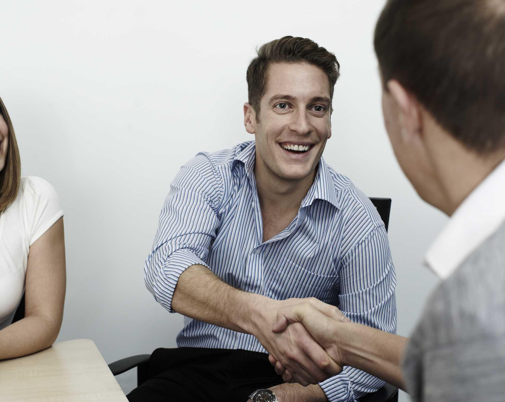 Hombre sonriendo mientras se da la mano