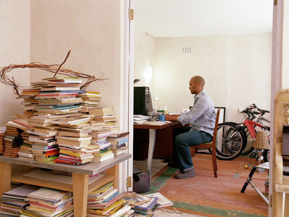 Man working in home office by bikes and books piled by doorway