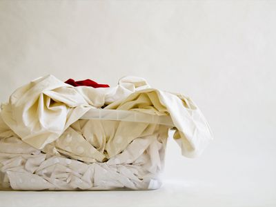 Red shirt in white laundry basket