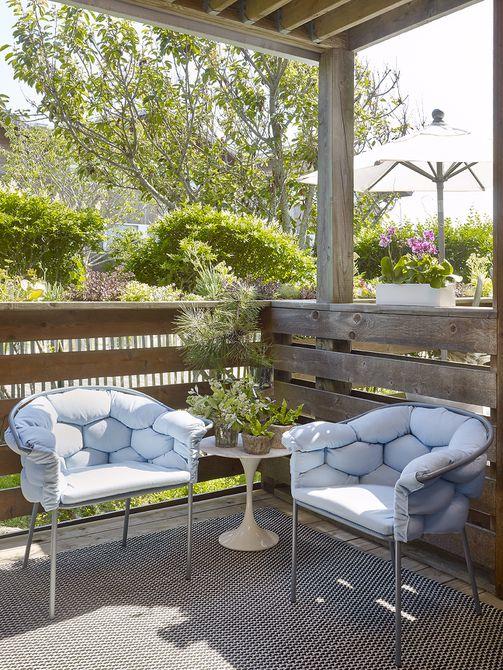 Un espacio cubierto al aire libre con sillas serpentinas Ligne Roset
