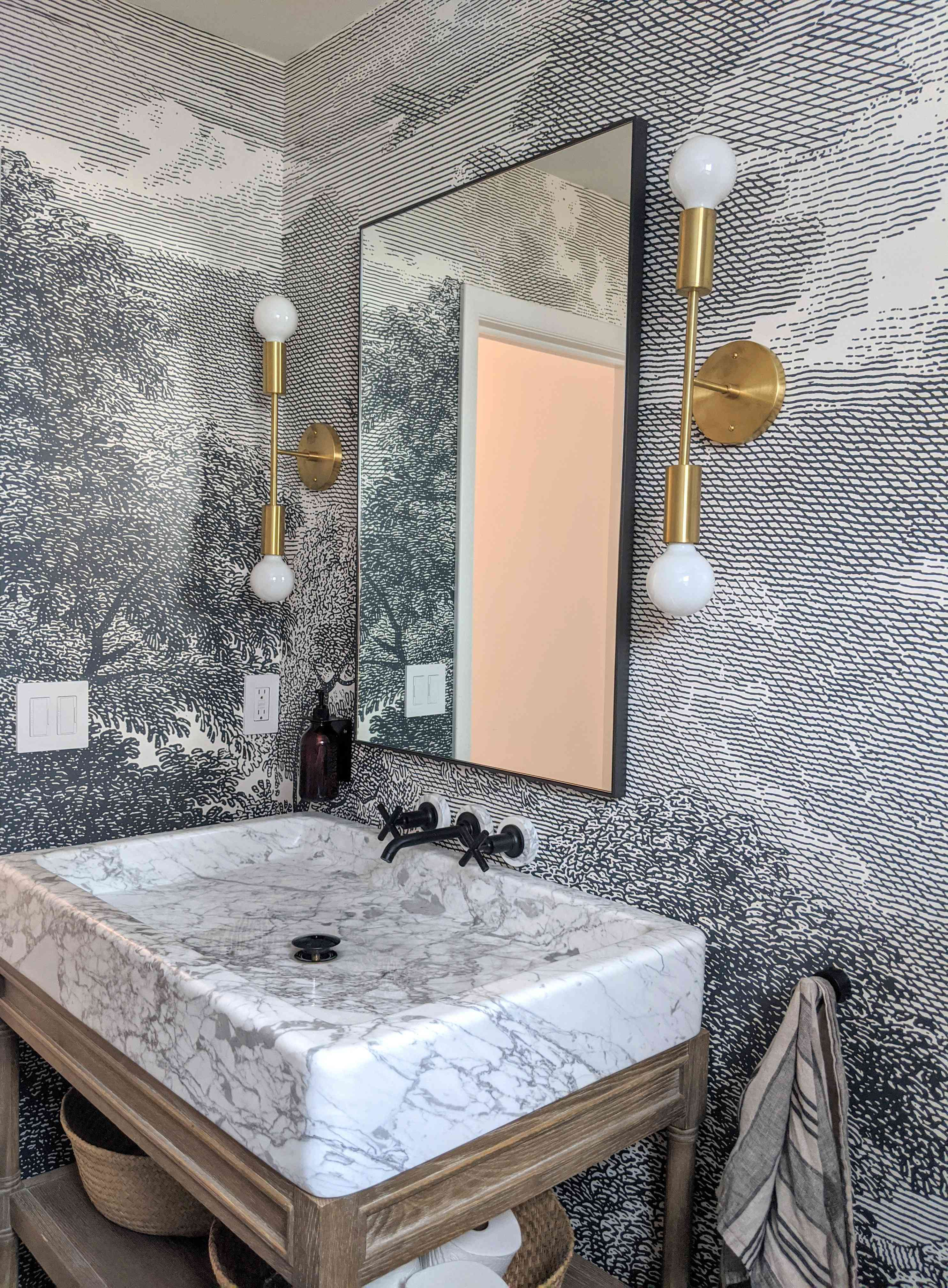 A bathroom in the Shaker Heights home of Molly and Fritz features graphic wall treatment, a rectangular marble sink, black hardware, and brass lighting