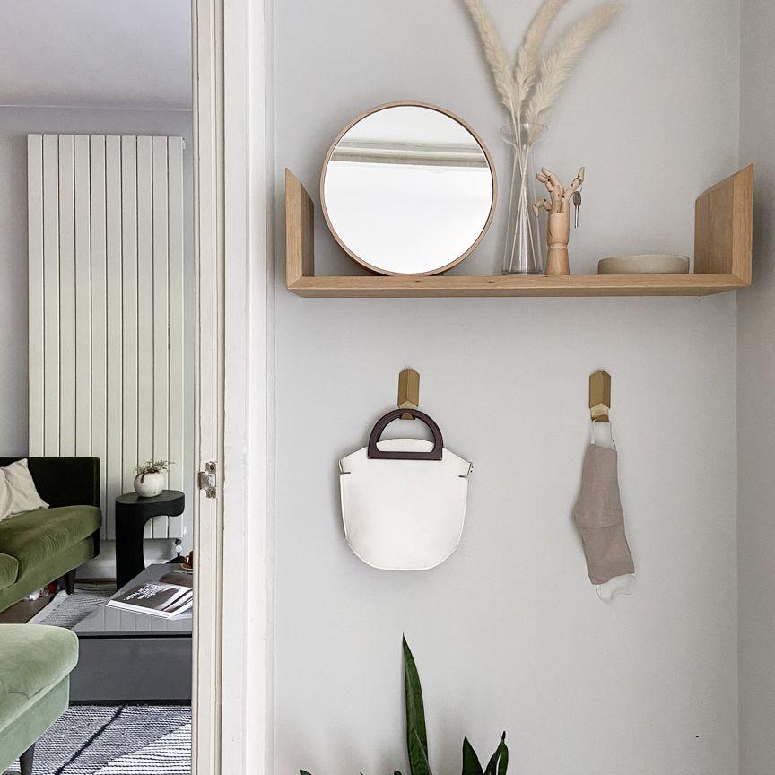 Natural wood mounted wall shelf with boho decor items