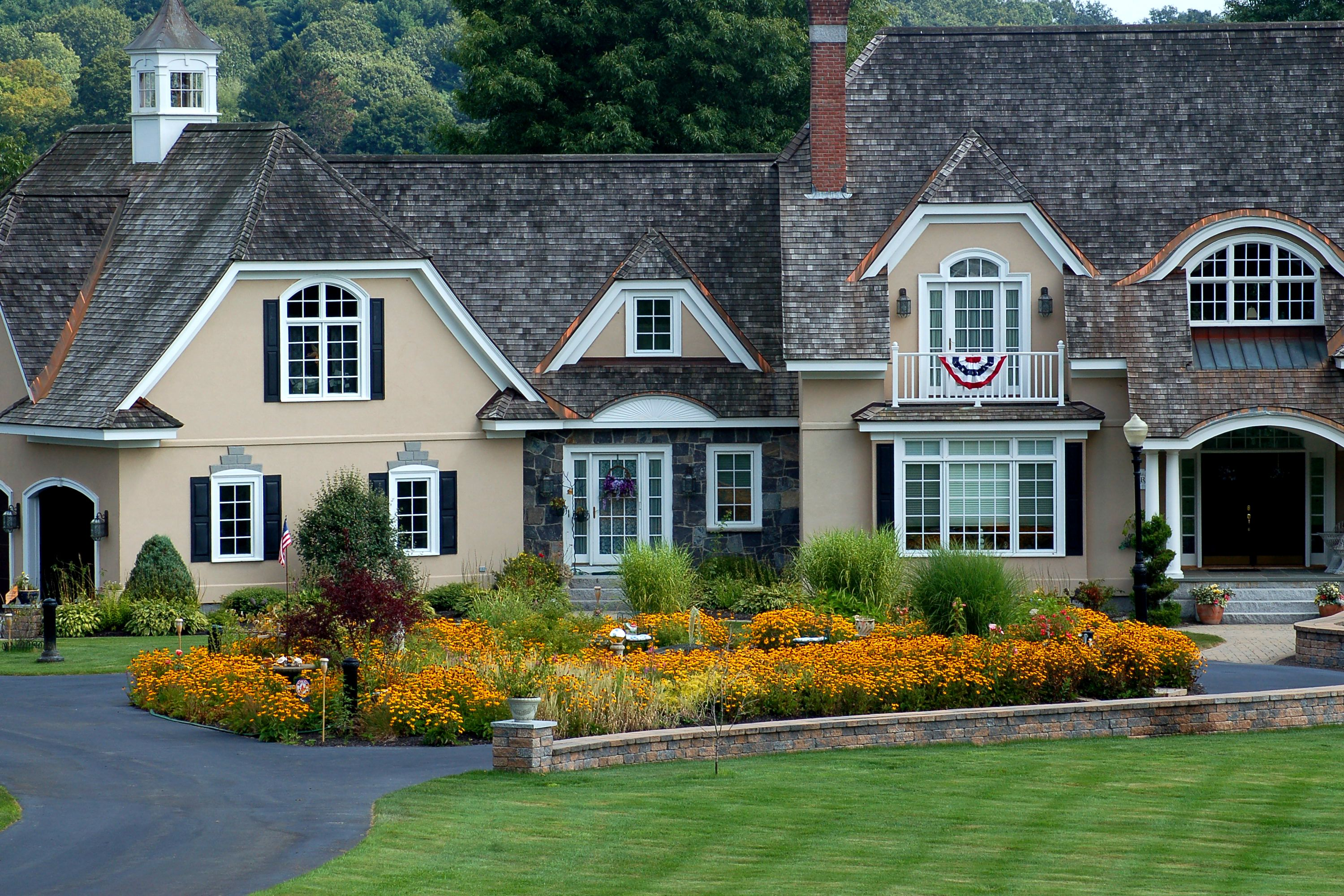 A large flower border in scale with its large house.