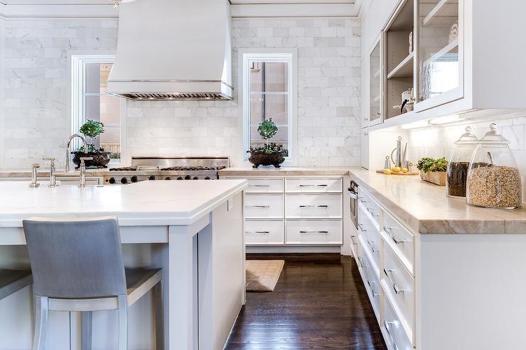 Mostrador hasta el techo protector contra salpicaduras de mármol en una cocina blanca