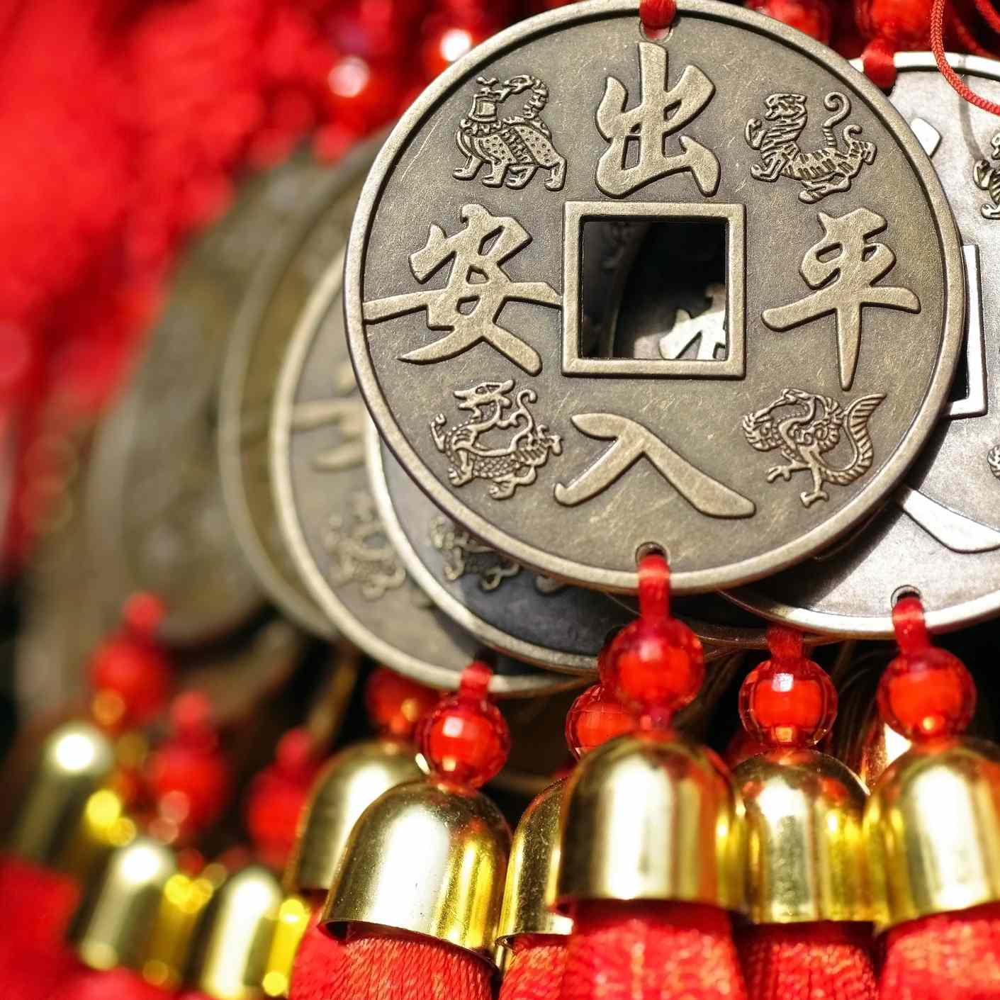 Red Chinese knot tassel ornaments, with large brass coins.