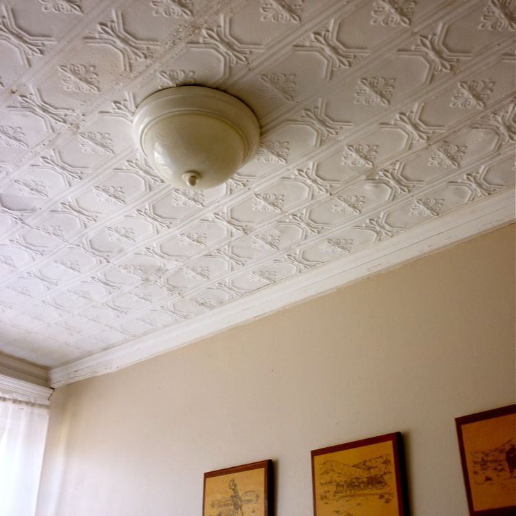Vintage tins adorning a ceiling with a light fixture in the middle.