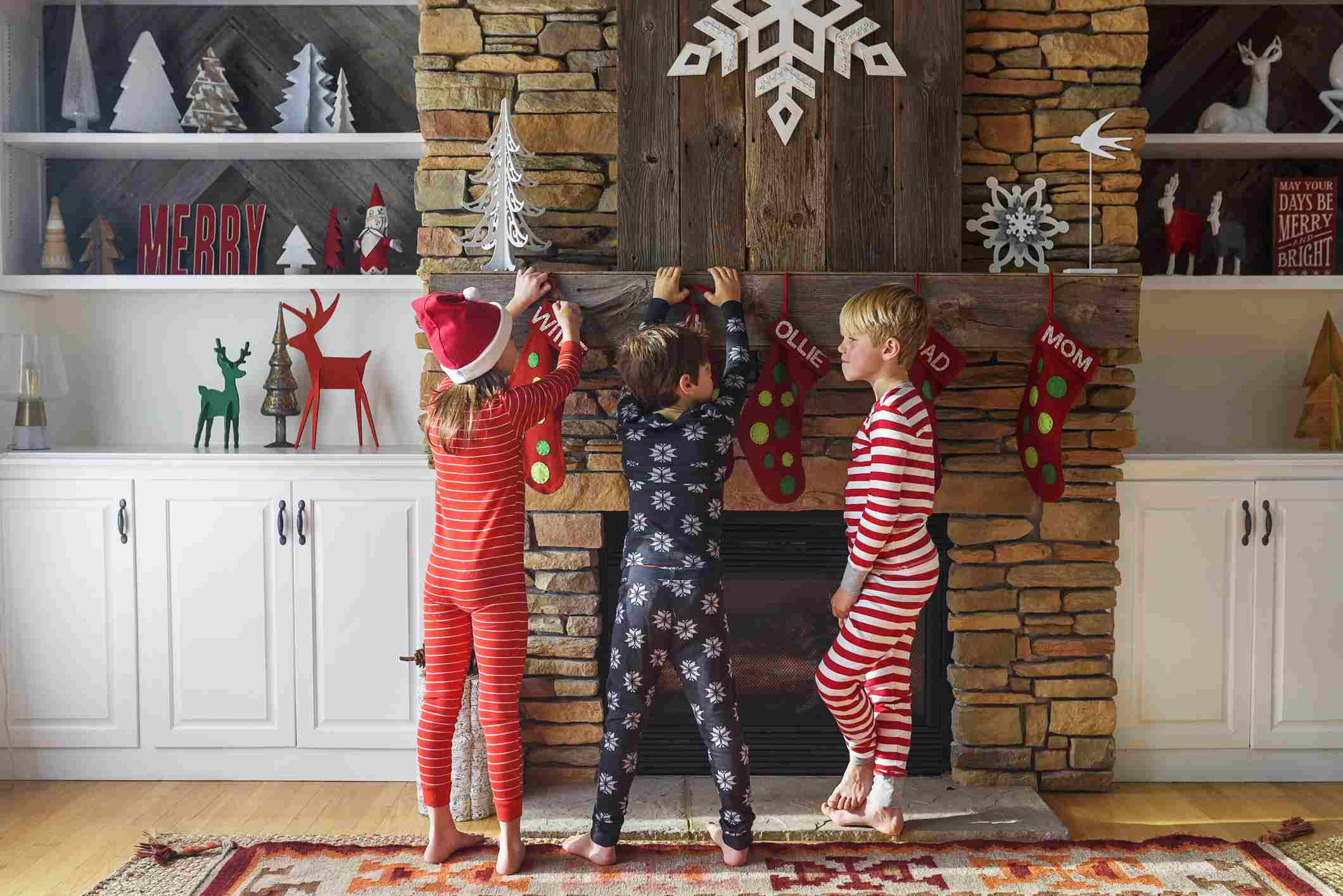 Three children hanging up Christmas stockings on a fireplace