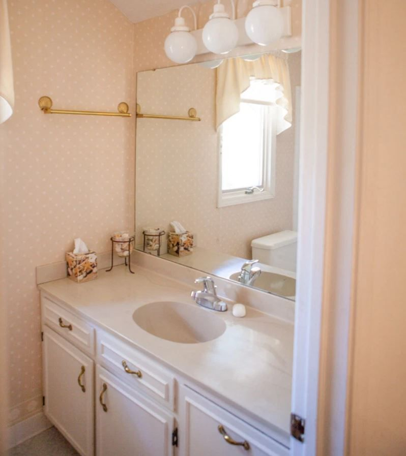 Light pink outdated bathroom vanity and wallpaper.