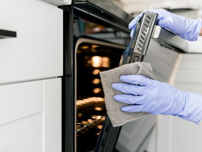 person cleaning an oven