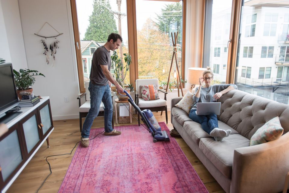 man vacuuming around family room