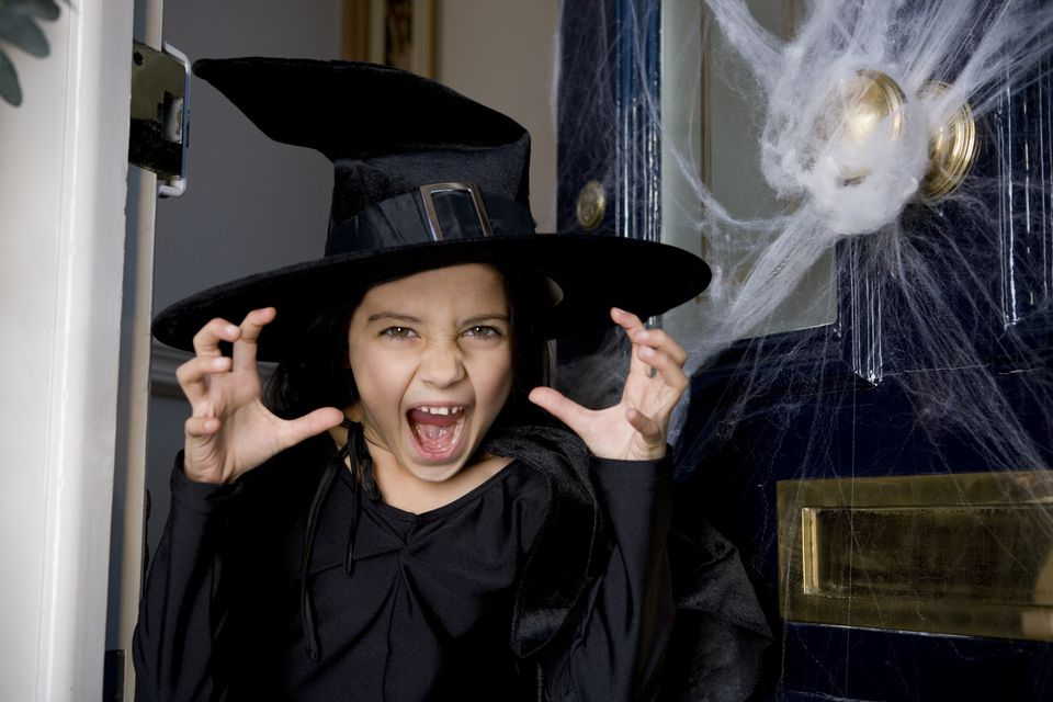Young girl at the front door, dressed up as a witch for Halloween